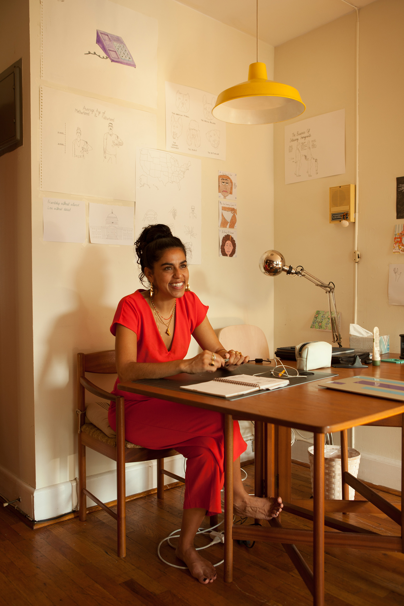 Mona Chalabi photographed in her workspace where sketches double as wallpaper.