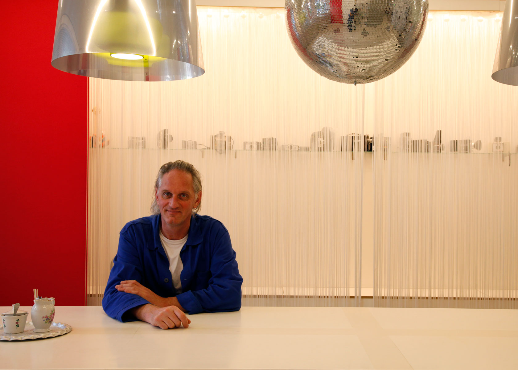 Kessels sitting under a disco ball in a red room with a large display of cameras