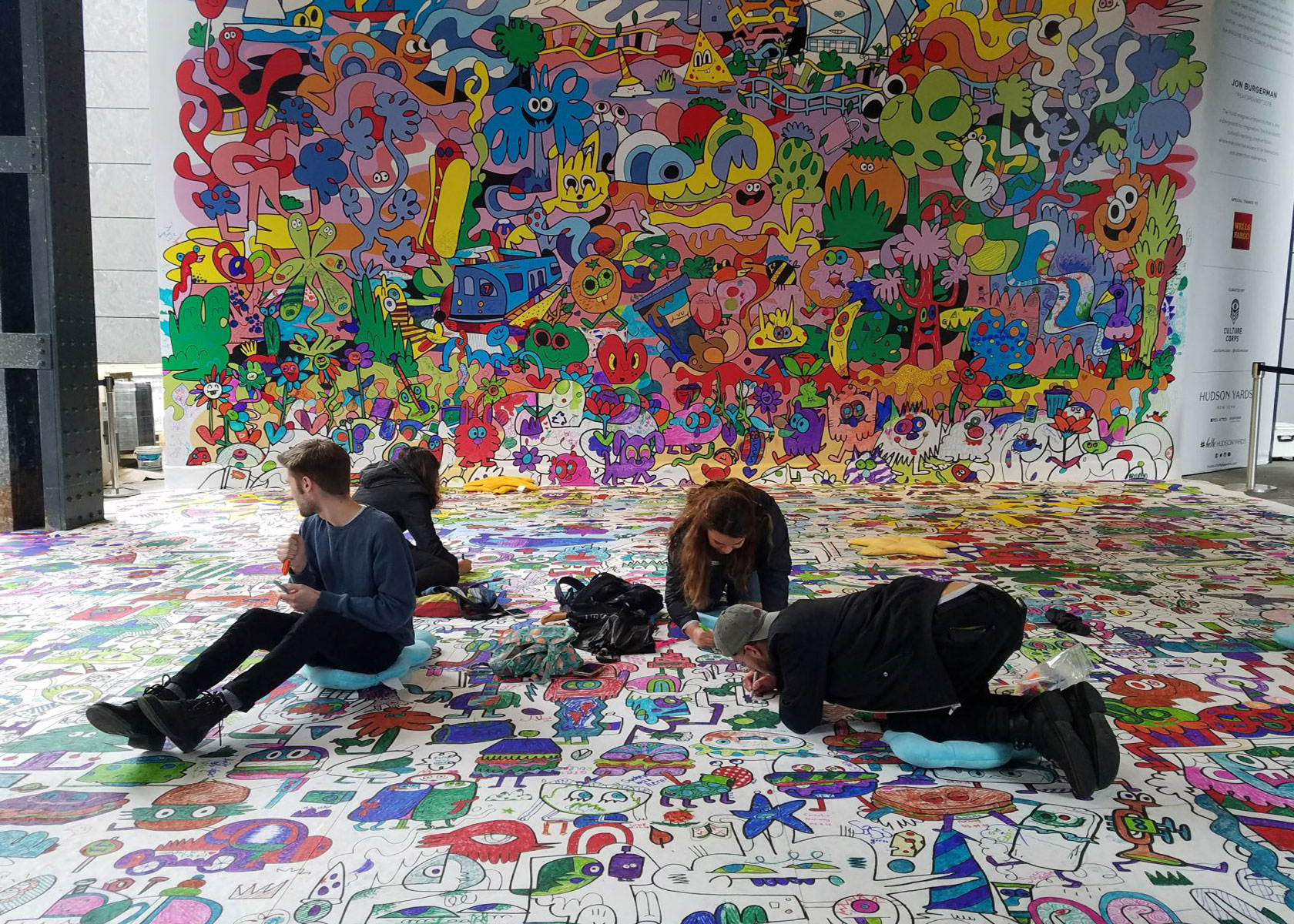 People coloring in a Burgerworld mural during an interactive art exhibit at Hudson Yards in Manhattan