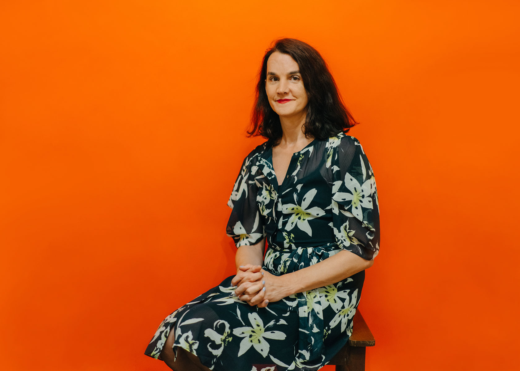 Uglow sporting a tropical dress sitting in front of an orange backdrop.