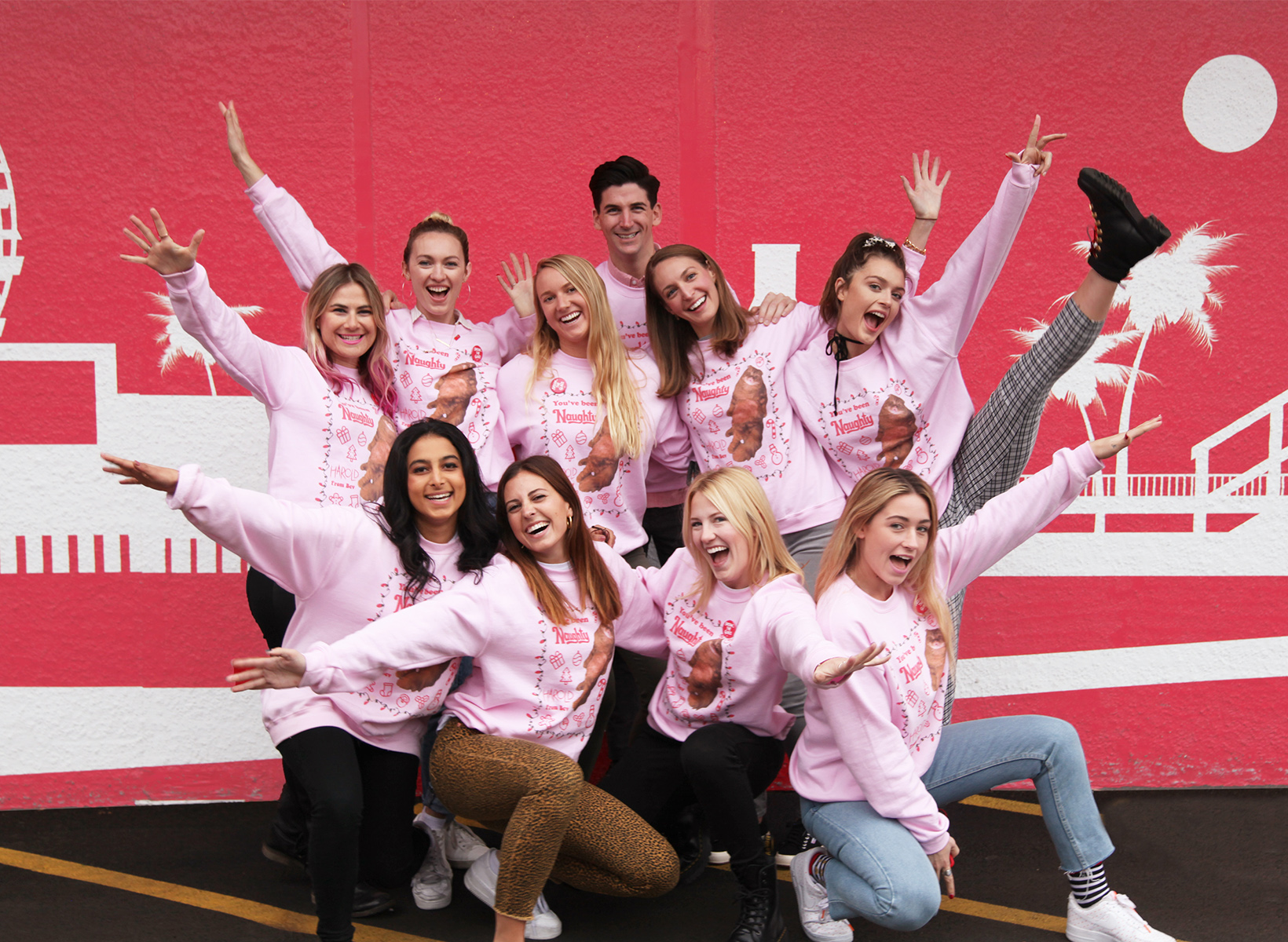 10 people pose for a high energy picture in pink sweatshirts