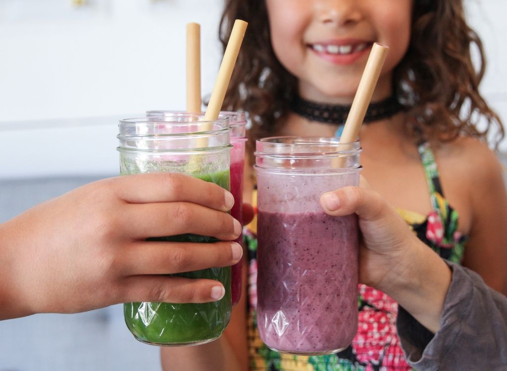 Children sip colorful smoothies out of bamboo straws.