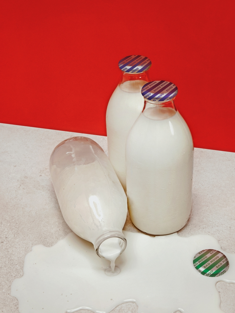 """A jug of milk with a cap that reads """"bad mood"""" spills over."""