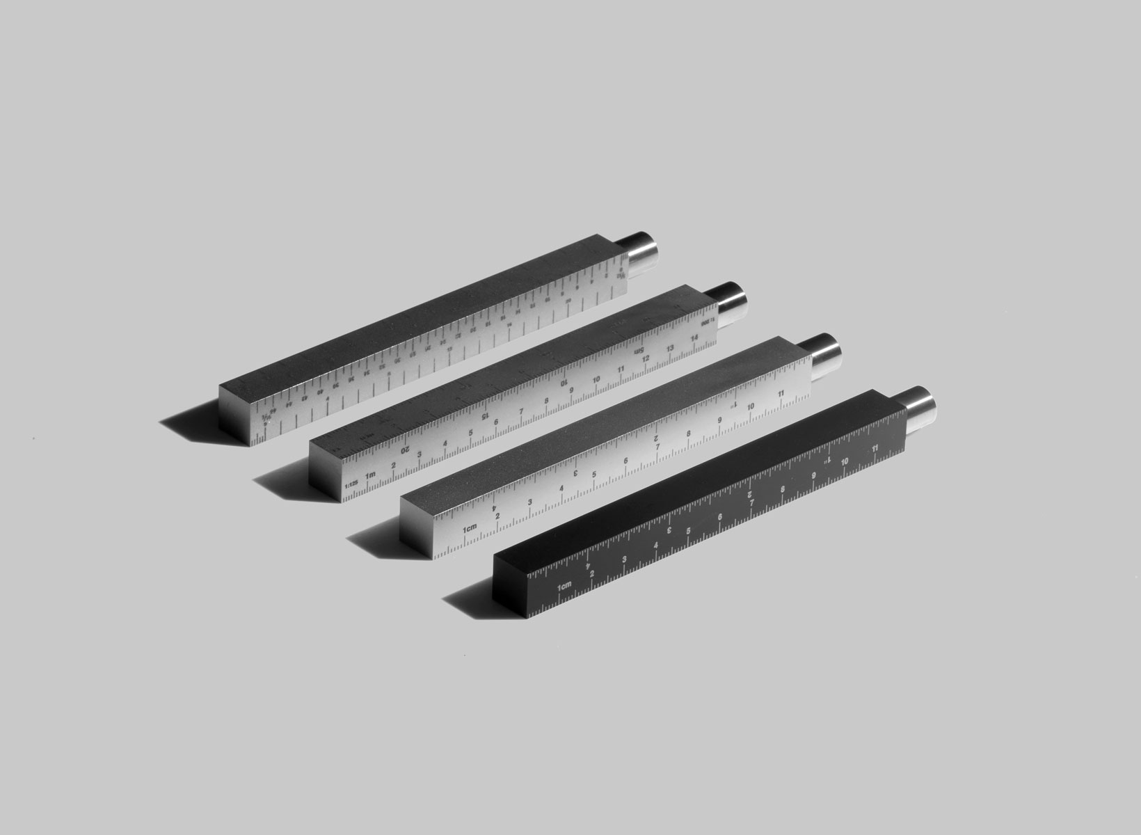 Four of the Type-A pen with ruler case laid on a grey background.