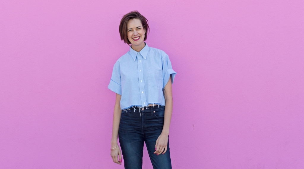 Ann Friedman in chambray shirt and jeans with a fuchsia background