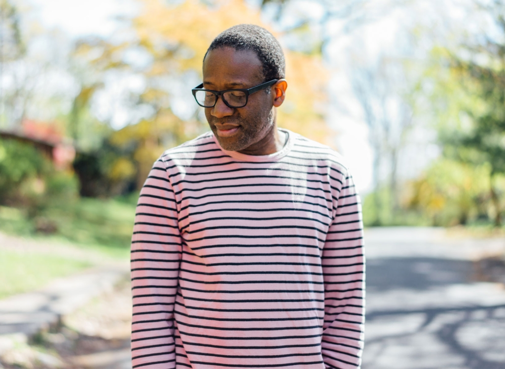 A man in a striped red shirt with glasses