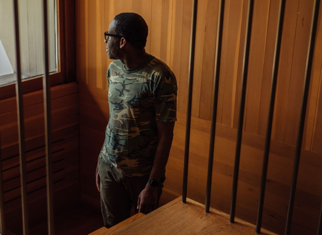 A man on a staircase looking away from the camera, wearing a camouflage shirt