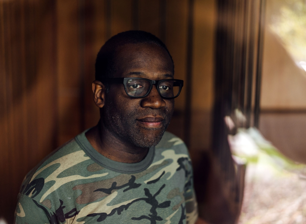 A headshot of a man in glasses wearing a camouflage shirt