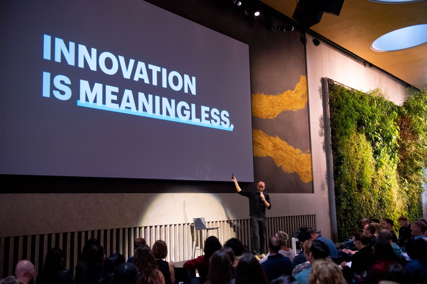 Alain Sylvain speaking at 99U Conference 2019 about innovation with slide stating that innovation is meaningless