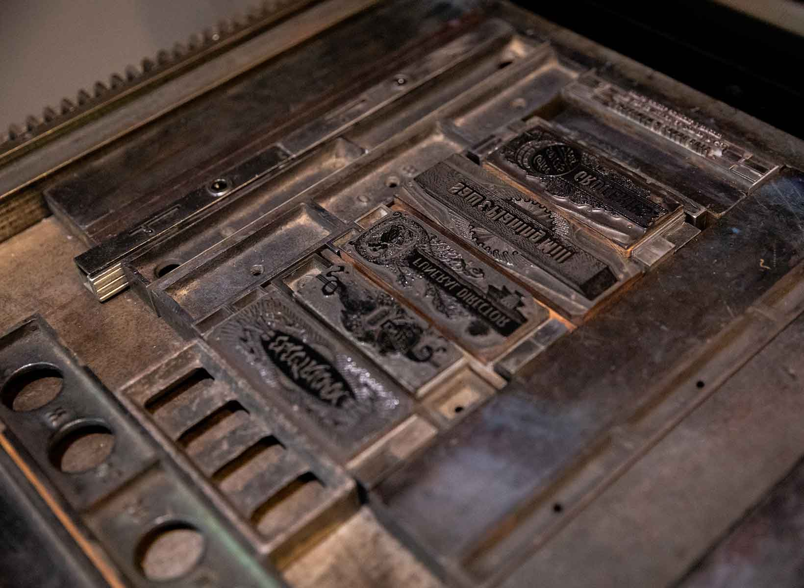 A closeup of the lead plates on a letterpress bed