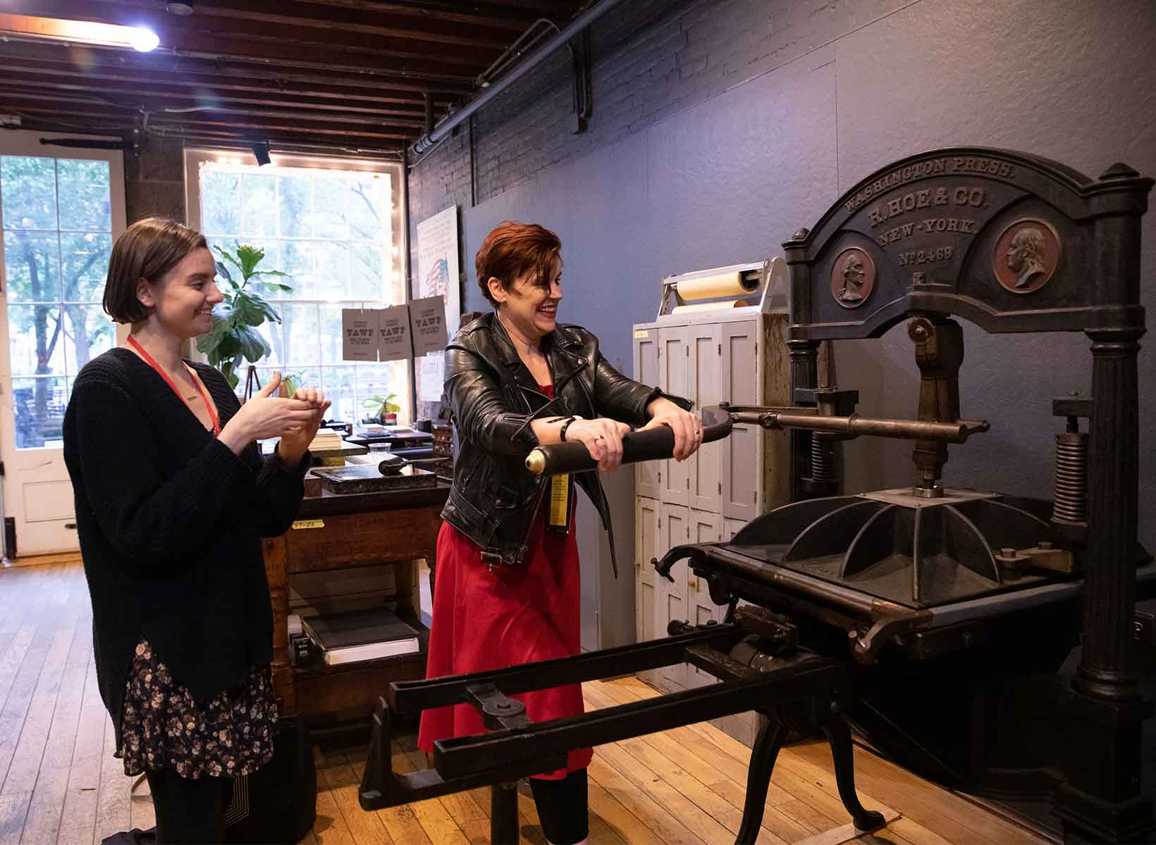 A woman in a red dress pulls on the lever of a letterpress