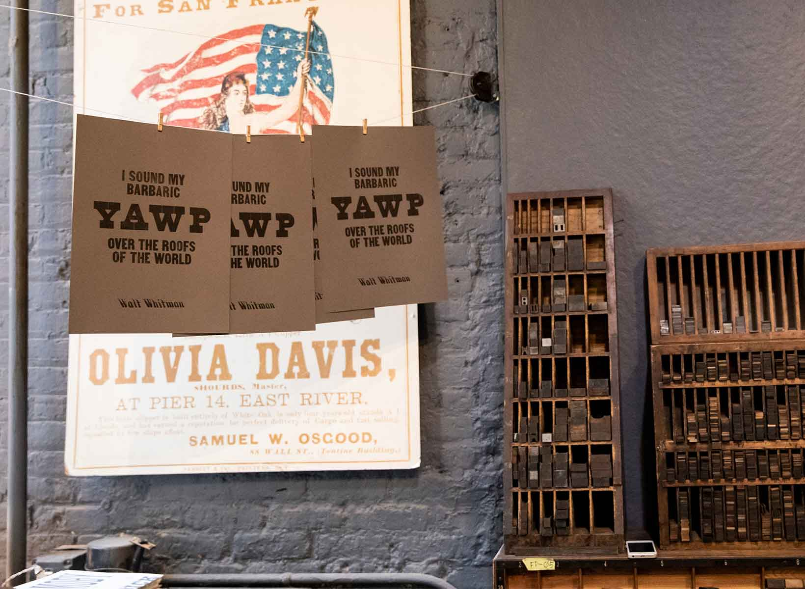 Posters hang on a line next to wooden trays of type