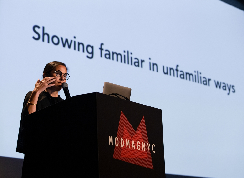 """A woman in glasses speaks into a microphone with the phrase """"Showing familiar in unfamiliar ways' on a slide behind her"""