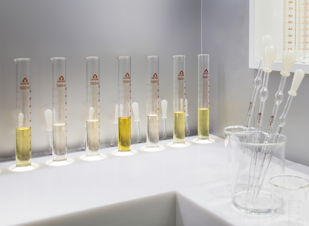 A row of beakers with yellow liquid in them