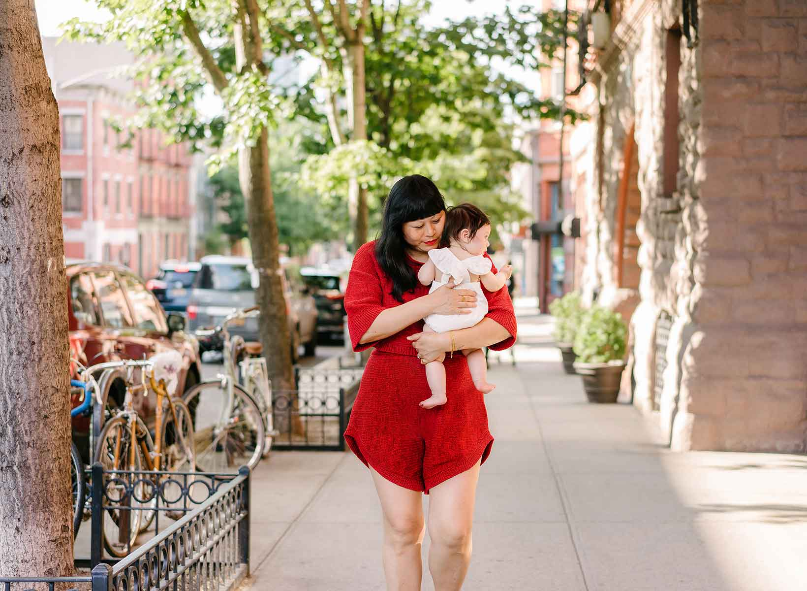 Picture of a woman in a red romper carrying a baby down a city street